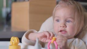 坐在桌上的逗人喜爱的小女孩使用与玩具和微笑对照相机 股票录像