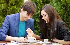 坐在桌上的年轻夫妇 库存照片