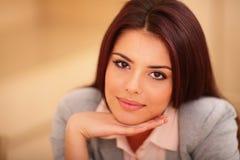 坐在桌上的年轻微笑的妇女 免版税库存图片