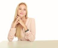 坐在桌上的年轻美丽的女孩 免版税库存照片