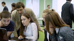 坐在桌上,小心地与膝上型计算机一起使用在教室和参加事务对策的人和 股票录像