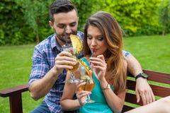 坐在桌后的夫妇在庭院里 免版税图库摄影