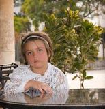 坐在桌后的庭院里的疲乏的小孩 免版税图库摄影