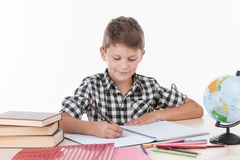 坐在桌和写上的逗人喜爱的男孩 免版税库存照片