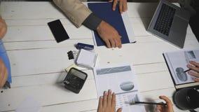 坐在桌和完成的上的顶视图工友与财政报告一起使用在办公室 男性和女性手  股票录像