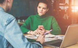 坐在桌和工作上的两个年轻女商人 图库摄影