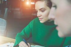 坐在桌和工作上的年轻女商人的特写镜头面孔 被弄脏的前景 采取在笔记本的女孩笔记 免版税图库摄影