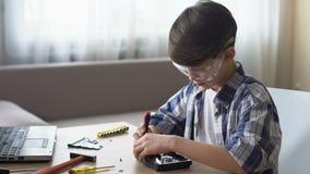 坐在桌和拆开的硬盘驱动器, IT爱好上的聪明的小男孩 股票视频
