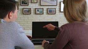 坐在桌和神色上的年轻夫妇在膝上型计算机屏幕 股票视频