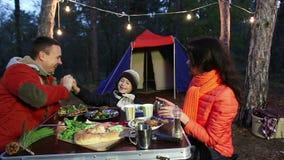 坐在桌和谈话,秋天森林上的愉快的年轻家庭 影视素材