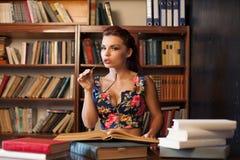 坐在桌学习参考书的玻璃的妇女图书管理员 免版税库存照片