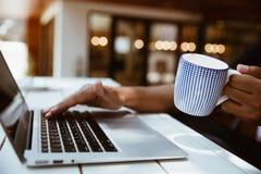 坐在桌键入的膝上型计算机键盘和h的年轻商人 库存照片