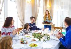 坐在桌附近和享用圣诞晚餐衣服的朋友 库存图片