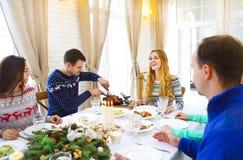 坐在桌附近和享用圣诞晚餐衣服的朋友 免版税库存照片