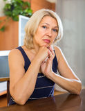 坐在桌附近的哀伤的成熟妇女 免版税库存图片