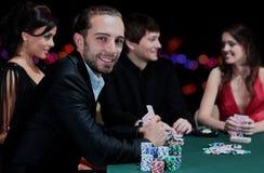坐在桌附近的打牌者在赌博娱乐场 免版税库存图片