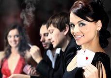 坐在桌附近的打牌者在赌博娱乐场 库存照片