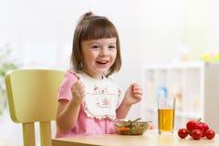 坐在桌食物的小孩立即可食在托儿所 库存照片