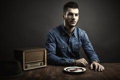 坐在桌,葡萄酒样式上的年轻人画象 免版税库存图片