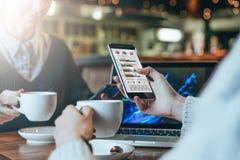 坐在桌,饮用的咖啡上和分析数据的两个年轻女商人 在桌膝上型计算机上 在网上学习的学生 库存照片