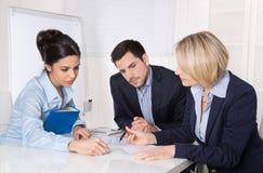 坐在桌talki的一个专业企业队的小组 免版税库存照片