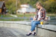 坐在桥梁文字的一个可爱的学生女孩的画象 库存图片