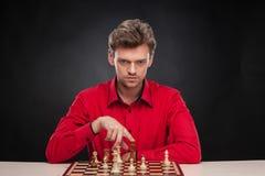 坐在棋的年轻偶然人 免版税库存图片