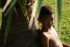 坐在棕榈下的男孩 免版税库存图片