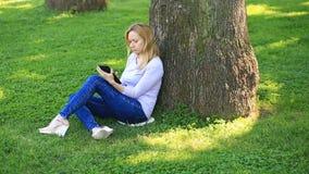 坐在棕榈树下和浏览互联网的英俊的妇女在智能手机 股票录像