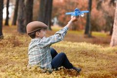 坐在森林和使用与玩具飞机的男孩 免版税库存照片