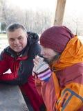 坐在森林和饮料的一个木眺望台的男人和妇女 免版税图库摄影