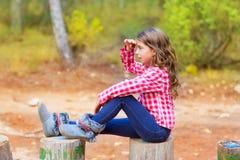坐在森林树干的孩子女孩很远查找 免版税图库摄影