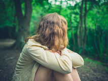 坐在森林里的少妇 免版税库存照片