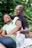 坐在森林里的愉快的爱恋的夫妇画象  免版税库存照片