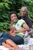 坐在森林里的愉快的爱恋的夫妇画象  免版税图库摄影