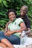 坐在森林里的愉快的爱恋的夫妇画象  库存图片