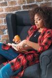 坐在椅子和学习与书的少妇,当吃苹果时 免版税库存图片