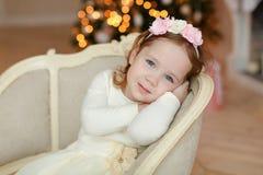 坐在椅子和微笑在Christm的小女孩卷曲婴孩 免版税库存图片