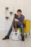 坐在椅子和拿着吉他的人 免版税库存图片