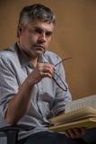 坐在椅子和阅读书的人 免版税图库摄影