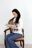 坐在椅子和读书的俏丽的女孩 工作室 免版税图库摄影