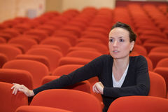 坐在椅子的一名妇女在音乐厅里 图库摄影