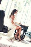 坐在椅子的一套美丽的婚礼礼服的迷人的新娘在窗口附近 免版税库存照片