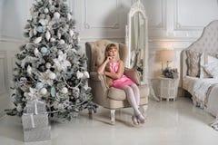 坐在椅子的一件淡粉红的礼服的女孩在圣诞树 库存图片