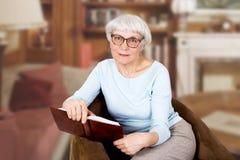 戴坐在椅子的书和眼镜的愉快的美丽的年长妇女 母亲 祖母 免版税库存照片