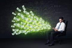 坐在椅子的商人拿着有美金的co片剂 免版税图库摄影