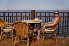 坐在椅子的女孩在大阳台由海 库存照片