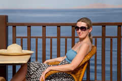 坐在椅子的女孩在大阳台由海 免版税库存图片