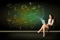 坐在椅子的女实业家拿着有媒介象的膝上型计算机 免版税图库摄影