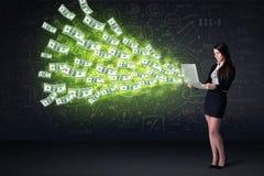 坐在椅子的女实业家拿着有美金的膝上型计算机 免版税库存图片